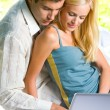 Young couple working with laptop, outdoor — Stock Photo