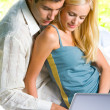 Young couple working with laptop, outdoor — Stock Photo #10795401