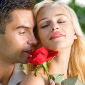 Giovane coppia felice con rosa, all'aperto — Foto Stock