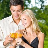 Jovem casal feliz com champanhe, ao ar livre — Fotografia Stock
