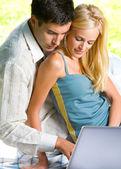 Casal jovem trabalhando com laptop, ao ar livre — Fotografia Stock