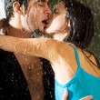 Young couple hugging under a rain - Foto Stock