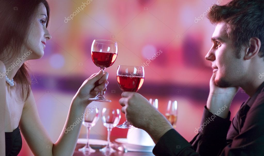 Young happy amorous couple with glasses of redwine on romantic date at restaurant  Stock Photo #11211173