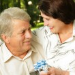Mature happy smiling couple embracing in park with gift — Stock Photo