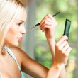 Young blond woman with makeup brush at home — Stock Photo
