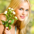 Cheerful woman with bouquet of white roses — Stock Photo #11548965