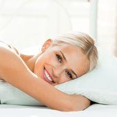 Jonge vrouw wakker op bed — Stockfoto