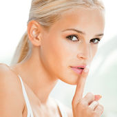 Beautiful blond woman with finger on lips — Stock Photo