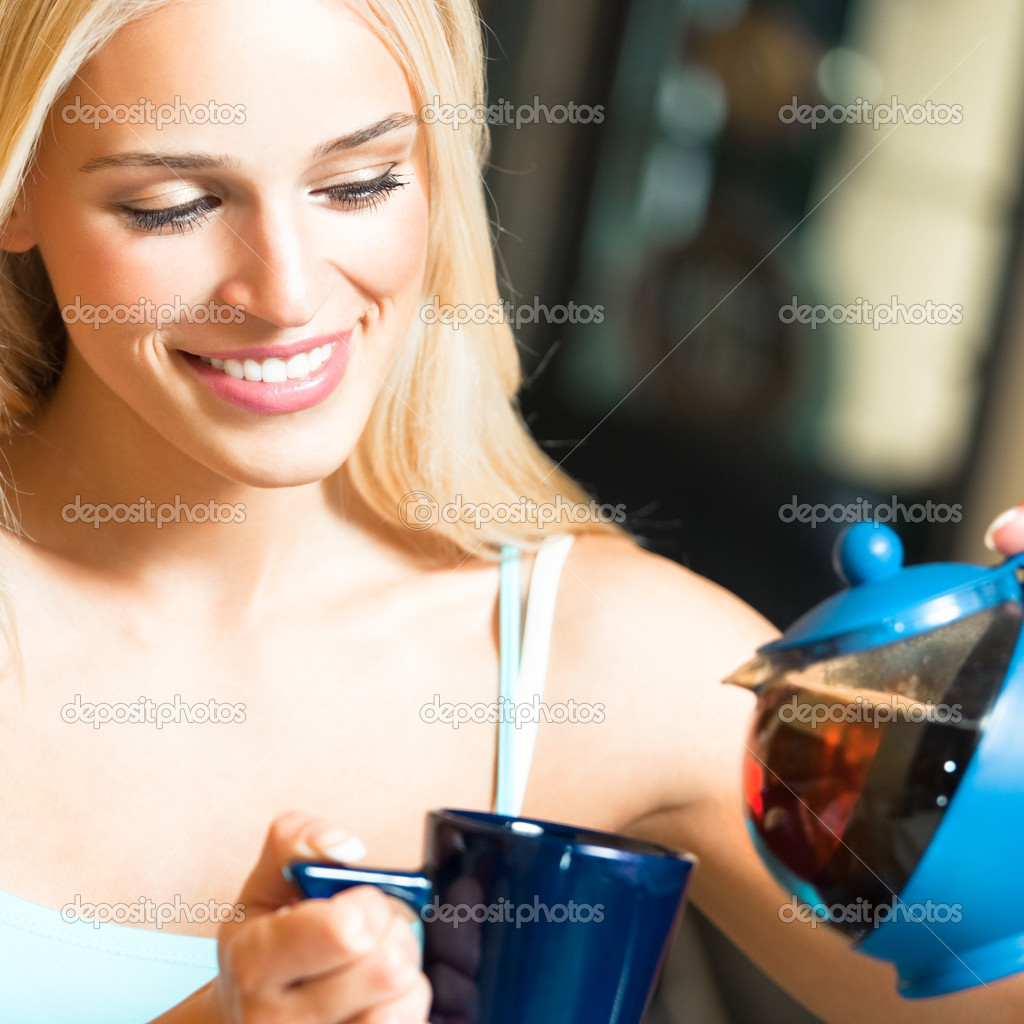 Happy smiling cheerful blond girl with teapot and cup, at home — Stock Photo #11548971