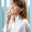 Young business woman with phone at office — Stock Photo #11931258