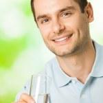 счастливый человек со стаканом воды, на открытом воздухе — Стоковое фото
