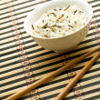 Plate with rice and chopsticks — Stock Photo