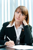 Young thinking businesswoman at office — Stock Photo