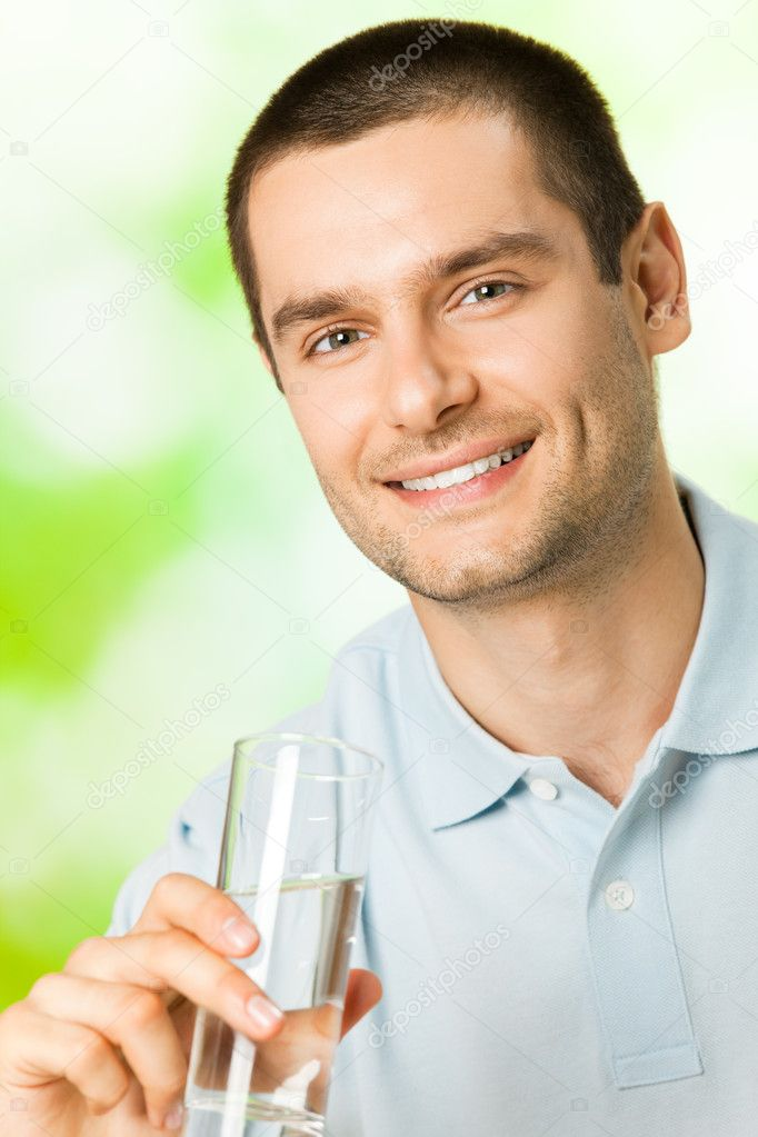 Portrait of young happy man with glass of water, outdoors  Stock Photo #11933752