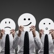 Businessmen holding smilies - Foto Stock