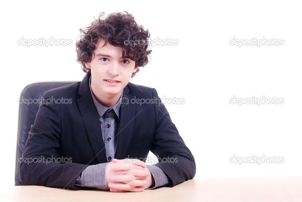 Young curly businessman or student sitting in front of an empy desk, on white background. — Stock Photo #11362053