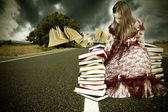 Girl with books flying time on the road — Stock Photo