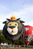 BARNEVELD, THE NETHERLANDS - 17 AUGUST 2012: Colorful lion and red air balloons taking off at international balloon festival Ballonfiesta in Barneveld on August 17 in Barneveld, The Netherlands — Stock Photo