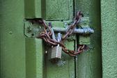 Una puerta verde con cadena y candado — Foto de Stock
