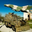 Military vehicle and MIG 21 airplane — Stock Photo