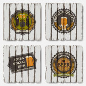 Beer badges and labels on old wood background — Stock Vector