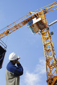 Building worker and giant cranes — Stock Photo