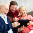 Family Uses Tablet PC and Laughs - Stock Photo
