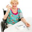 Disabled Senior Monitors Her Blood Pressure - Stock Photo
