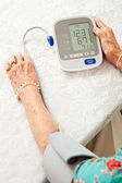Senior Woman Taking Blood Pressure — Stock Photo