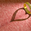 Wedding ring casting a heart on pink cloth — Stock Photo #12039099
