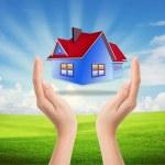 作为房地产业务的象征蓝天手中的房子 — 图库照片