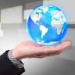 Business hand holding cystal globe on a touch screen background — Stock Photo