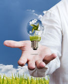 Paddle , windmill and blue sky in light bulb on hand — Stock Photo