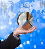 Affärsman som innehar paj diagram med världen karta bakgrund — Stockfoto