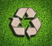 Recycle знак на зеленой траве — Стоковое фото