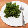 Fresh bunch of parsley on the plate with a fork on a wooden tabl — Foto de Stock