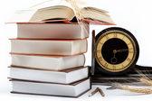 Una pila di libri e orologio antico su sfondo bianco. — Foto Stock