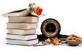 Een stapel boeken en antieke klok op een witte achtergrond. — Stockfoto
