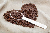 Heart of the coffee beans and wooden spoon on sacking — Foto Stock