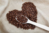 Heart of the coffee beans and wooden spoon on sacking — Stock Photo