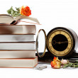 A stack of books and antique clock on a white background. - Stock Photo