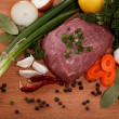 Raw meat, vegetables and spices isolated on a wooden table. - Stock Photo