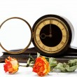 图库照片: Dry roses and antique wooden table clockon white background.