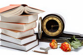 A stack of books and antique clock on a white background. — Stock Photo