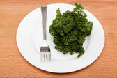 Fresh bunch of parsley on the plate with a fork on a wooden tabl — Stock Photo