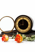 Dry roses and antique wooden table clockon a white background. — Stock Photo