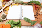 Notebook for recipes and spices on wooden table — Stock Photo