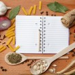 Foto Stock: Notebook for recipes and spices on wooden table