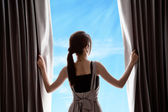 Young woman opening curtains and blue sky — Stock Photo