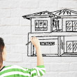 Woman draw house on brick wall — Stock Photo